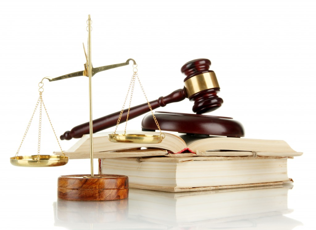 Golden scales of justice, gavel and books isolated on white